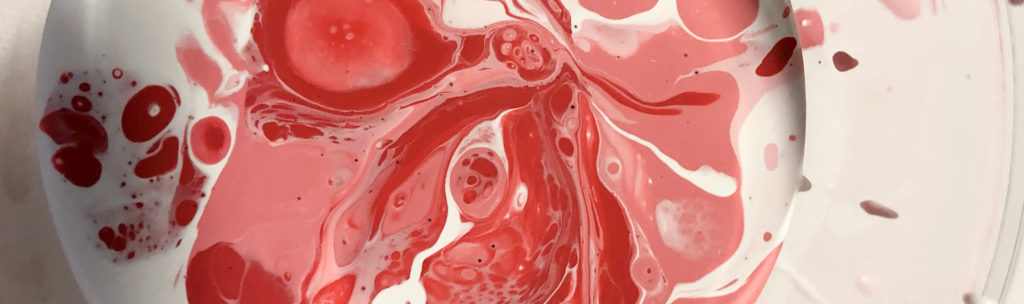close-up photo different colors of paint swirled in a cup