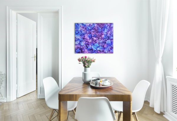 Purple painting on light wall in a dining room with a table and chairs in the room.
