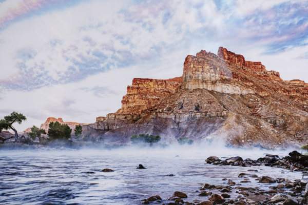Photo print on metal of the perspective at a rocky shore line looking at the Green River in Utah, witha large rocky mountionous structure in the background against a pink and blue cloudy streaked sky with mist rising from the waters.